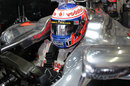 Jenson Button waits in his car in the McLaren garage