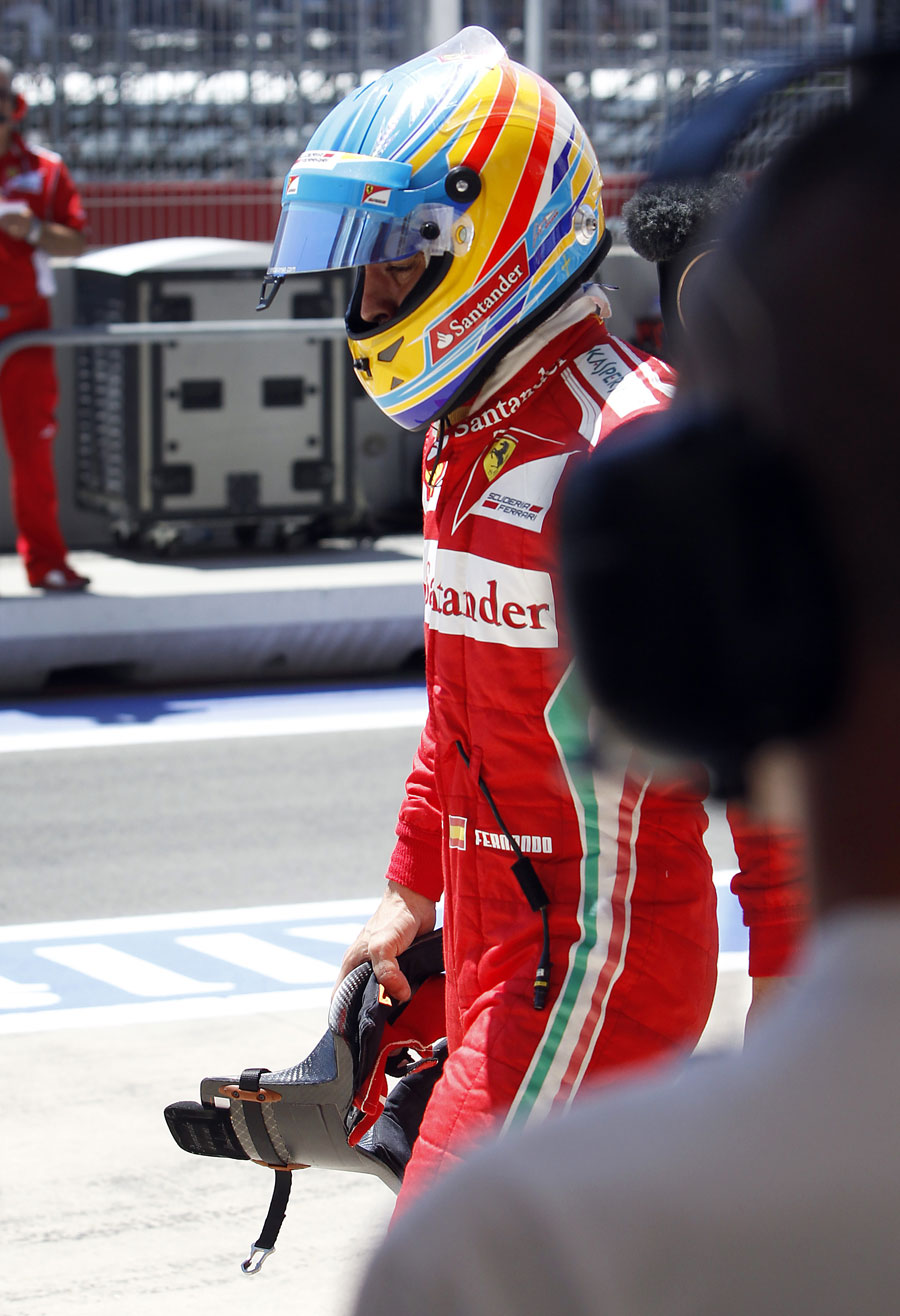 Fernando Alonso walks back after being eliminated in Q2
