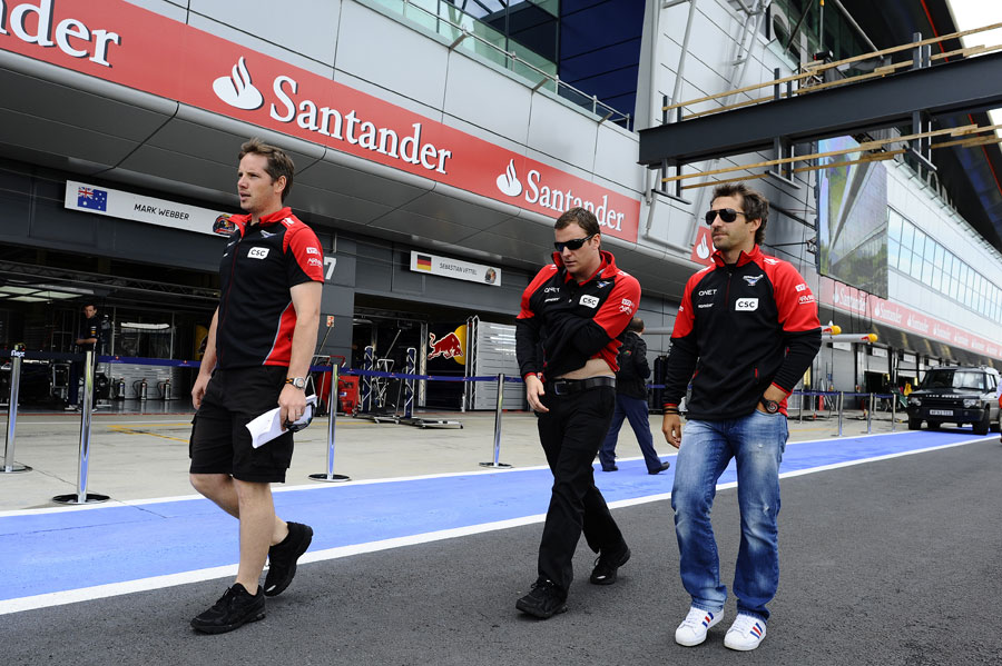 Timo Glock walks the track with his engineers on Thursday