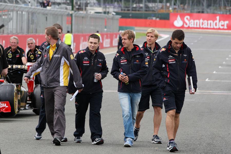 Sebastian Vettel walks the track with his team of engineers