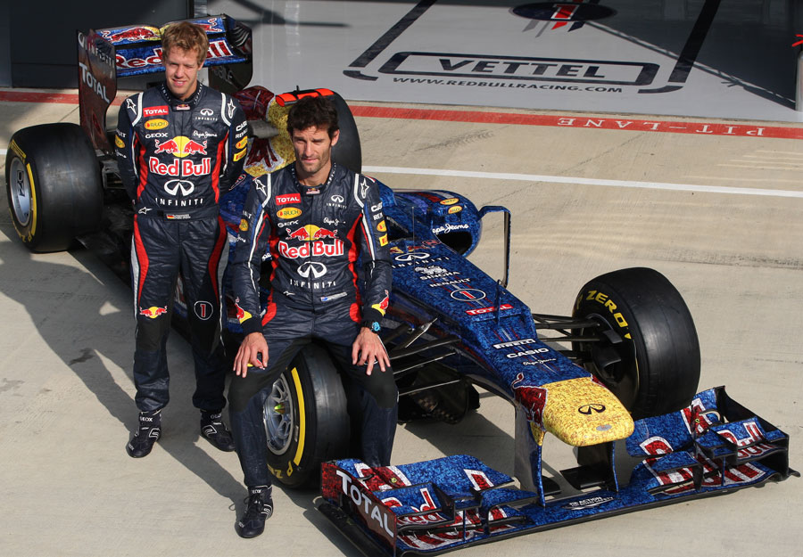 Sebastian Vettel and Mark Webber pose with the Red Bull in its one-off Faces for Charity livery