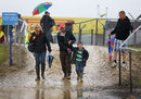 Spectators pick their way through the mud and water