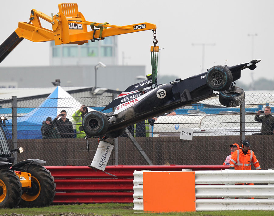 Bruno Senna's Williams is craned away after aquaplaning off the circuit in FP2