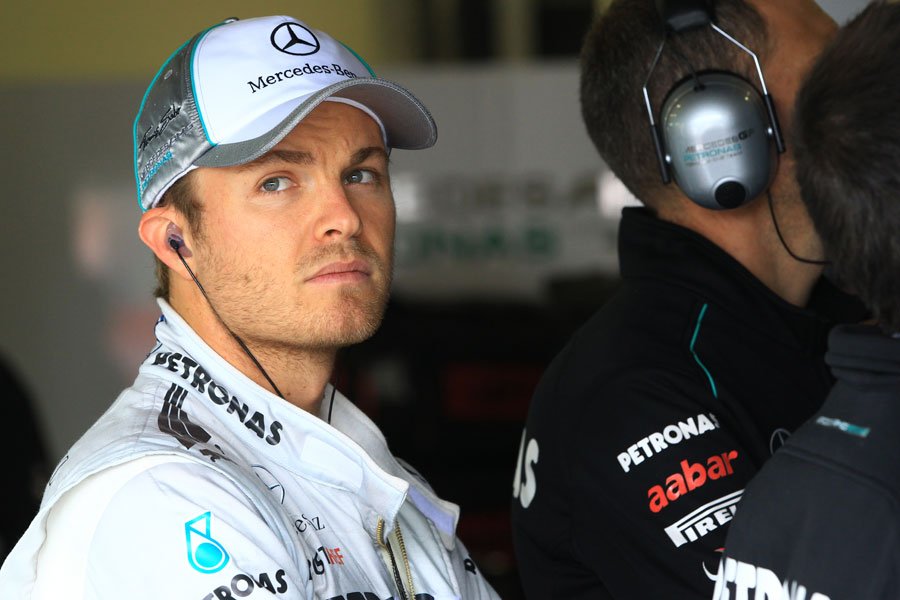 Nico Rosberg watches on from the garage during a rain delay