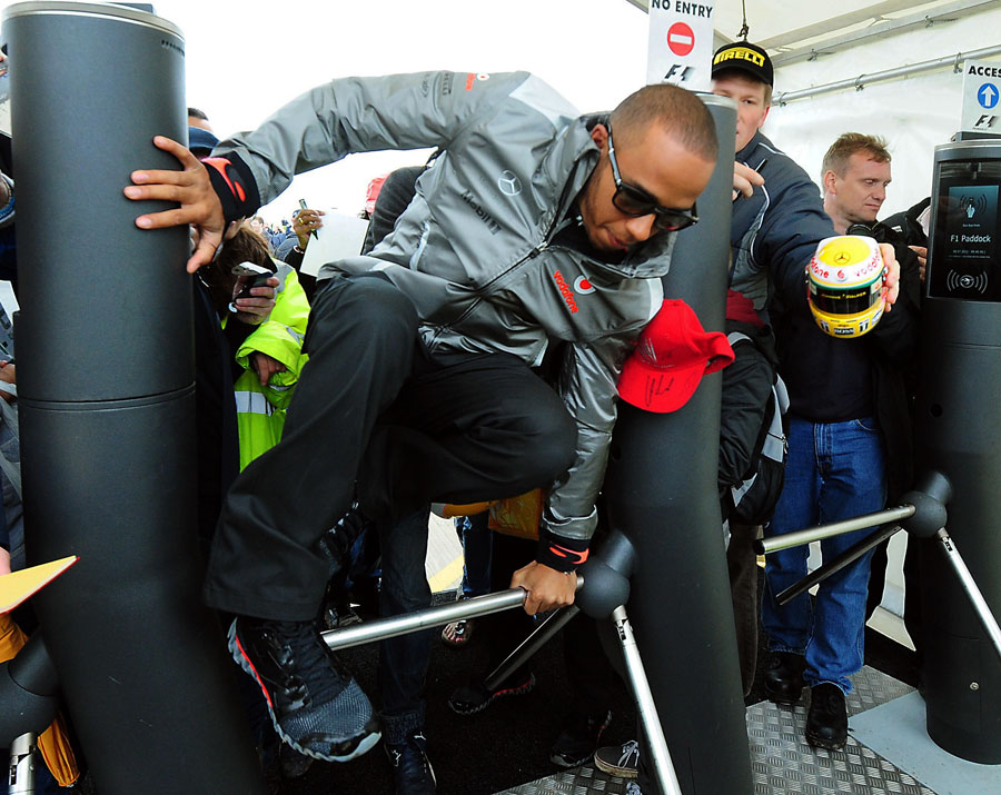 Lewis Hamilton hurdles the barriers on his way into the paddock