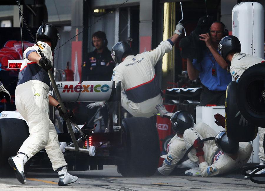 Kamui Kobayashi hits his pit crew at his second pit stop