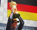 Mark Webber holds his trophy aloft