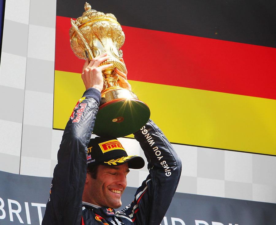 Mark Webber holds his trophy aloft