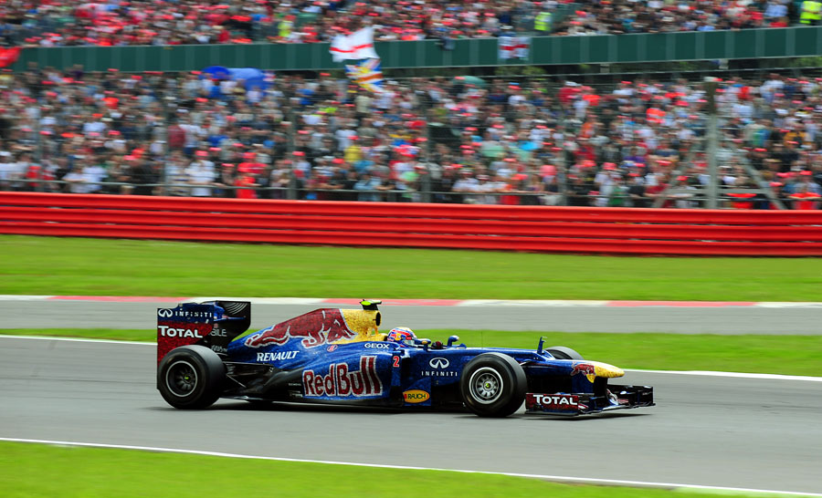 Mark Webber passes a packed grandstand