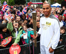 Lewis Hamilton holds the Olympic Flame before his Torch Relay leg through Luton