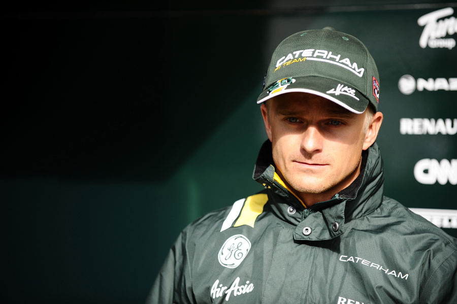 Heikki Kovalainen prepares to face the press during a break in the weather
