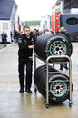 A Mercedes mechanic pushes hard tyres through the wet paddock