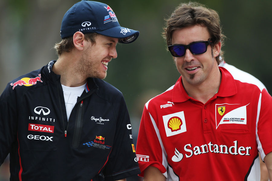 Sebastian Vettel and Fernando Alonso share a joke in the paddock