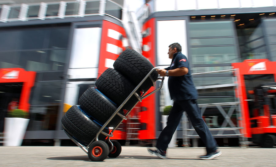 A Toro Rosso team member collects a set of wet weather tyres