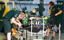 Caterham mechanics work on one of the cars in the garage on Wednesday
