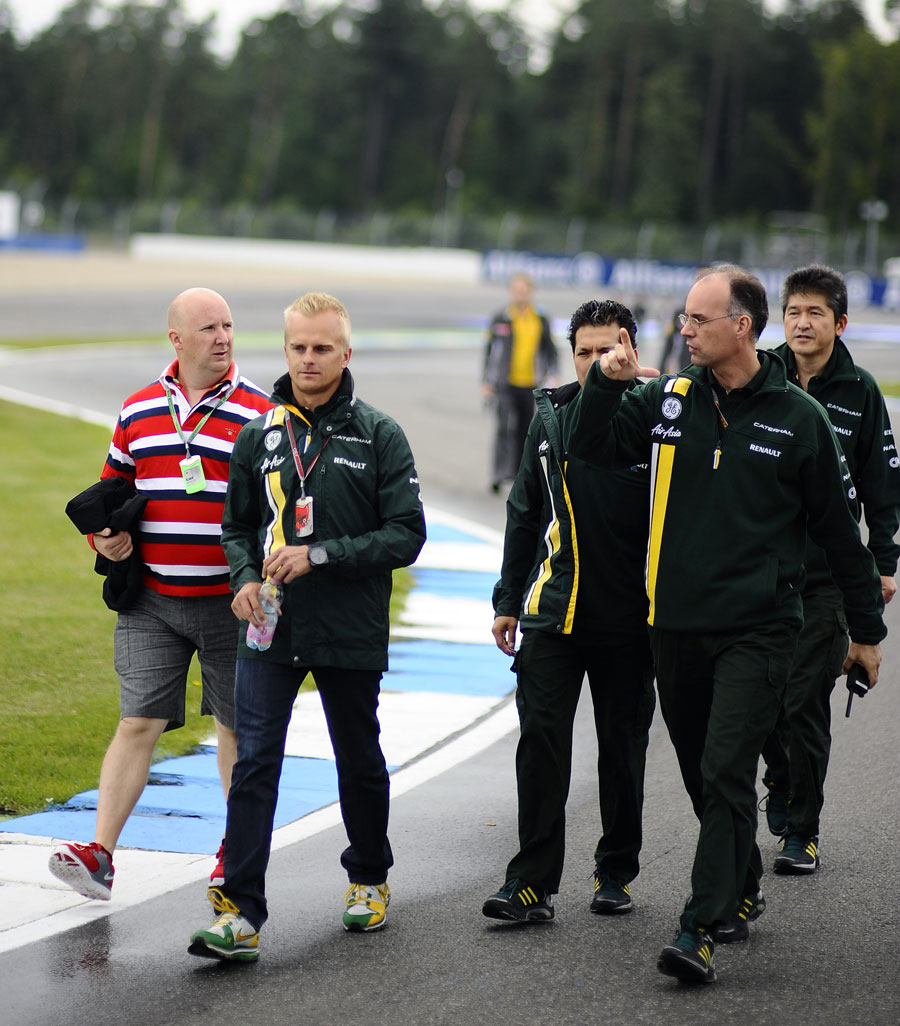 Heikki Kovalainen walks the track with members of the Caterham team