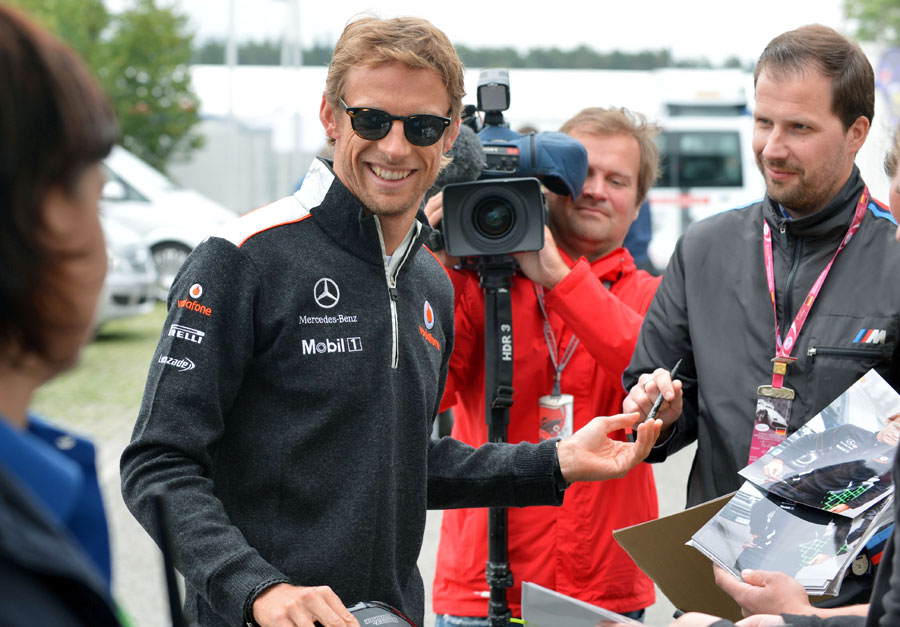 Jenson Button in relaxed mood as he signs autographs for the fans