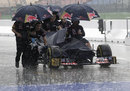 Toro Rosso mechanics get caught in a downpour as they retrieve a car from the weighbridge after FP3