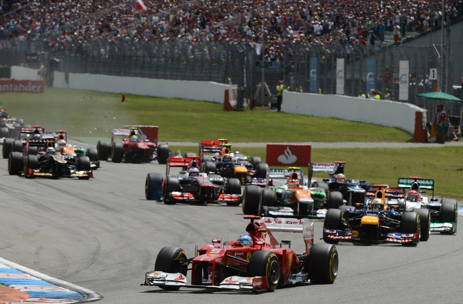 Fernando Alonso leads the field into the first corner as Felipe Massa makes contact in the background