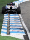 Mark Webber rides the kerbs on corner exit