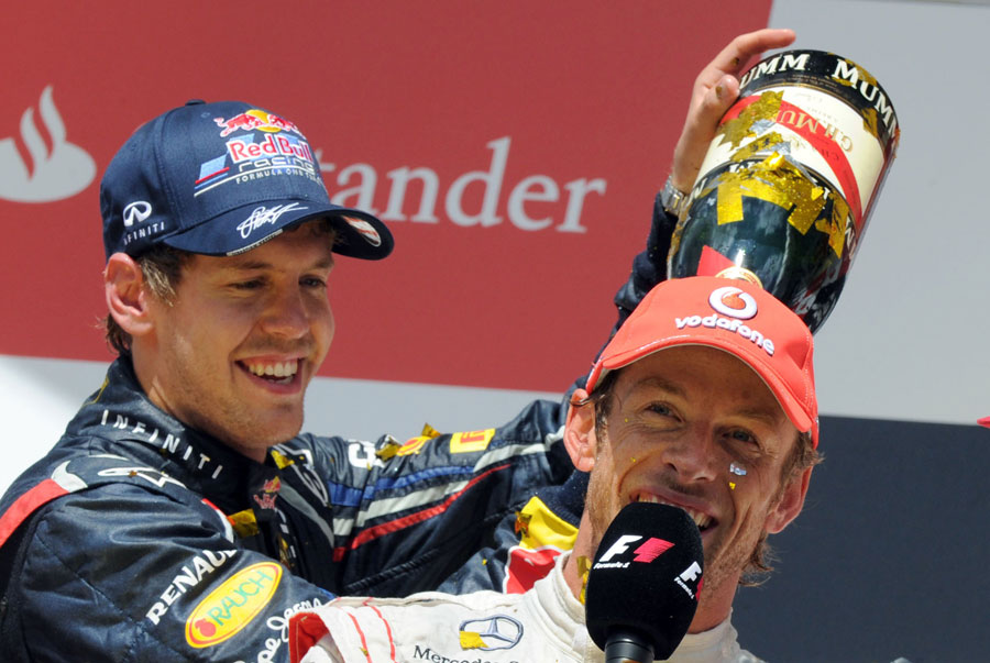 Sebastian Vettel pours champagne down Jenson Button's neck on the podium