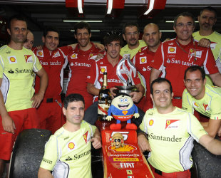 Fernando Alonso celebrates with his team and car after winning the German Grand Prix