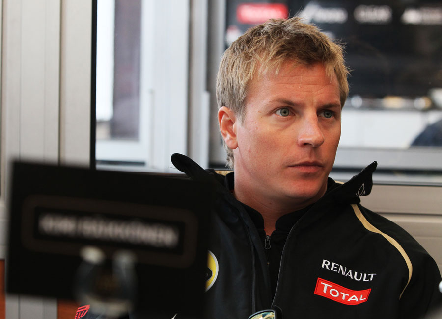 Kimi Raikkonen speaks to the press in the Lotus motorhome