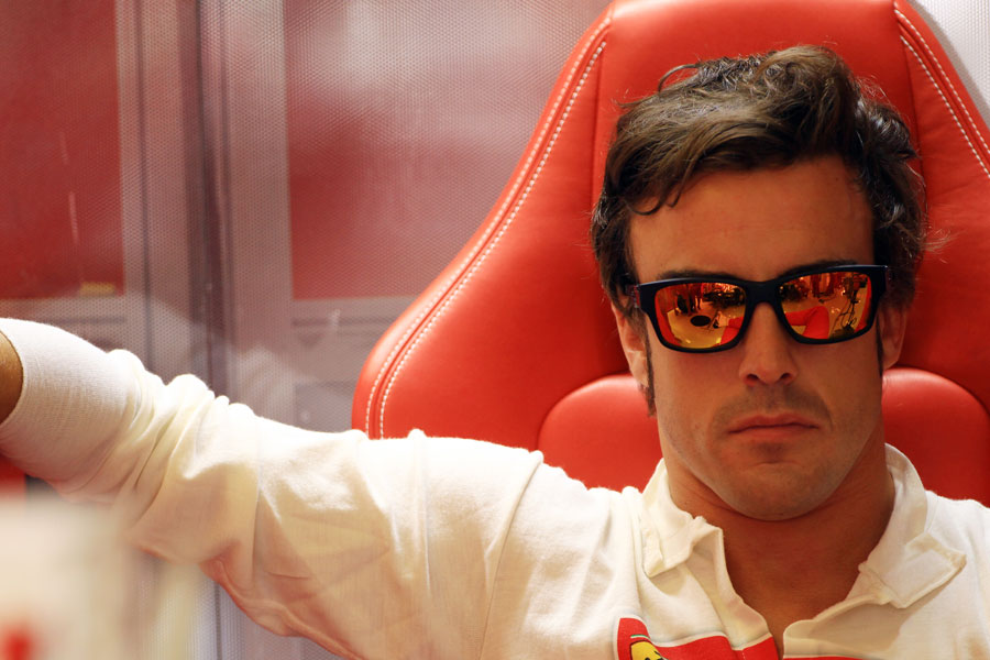 Fernando Alonso looks focused at the back of the Ferrari garage