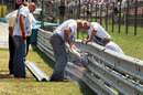 Track workers repair the Armco on the pit straight after an accident in the GP2 race on Sunday morning