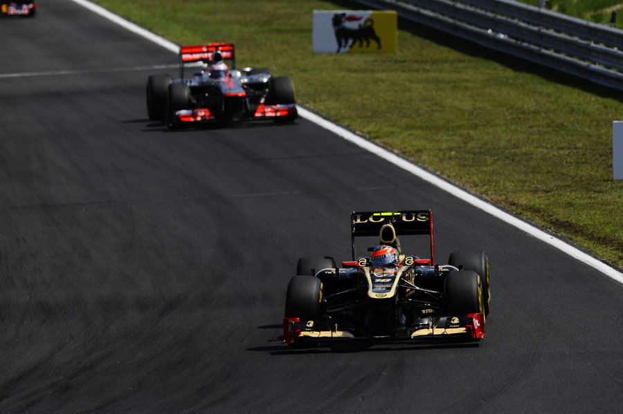Romain Grosjean leads Jenson Button early in the race