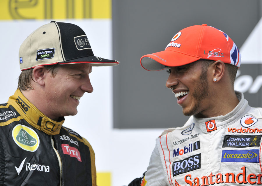 Kimi Raikkonen and Lewis Hamilton share a joke on the podium