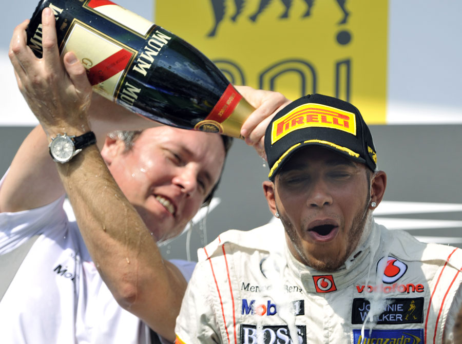 Sam Michael pours champagne down Lewis Hamilton's neck on the podium