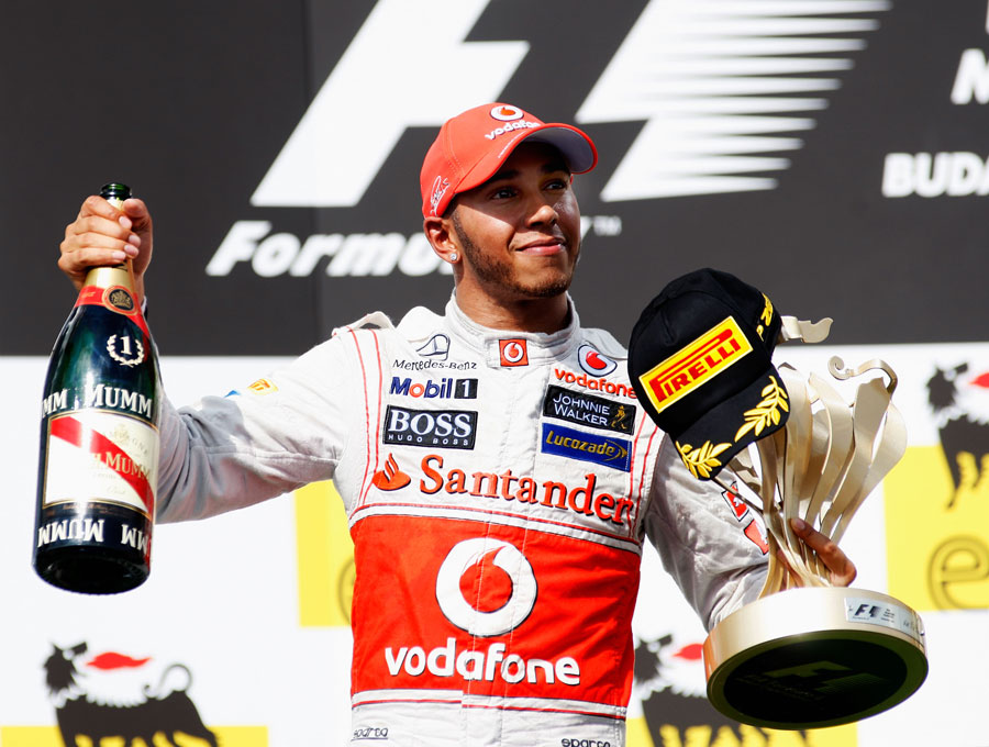Lewis Hamilton celebrates with his trophy on the podium