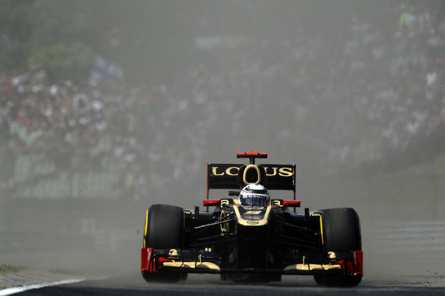Kimi Raikkonen emerges through a cloud of dust