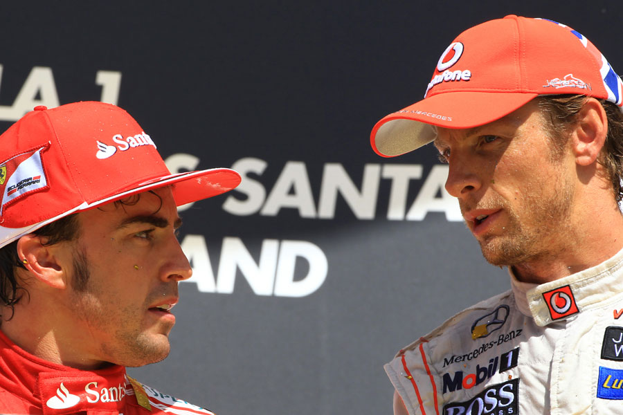 Jenson Button and Fernando Alonso talk on the podium