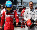 Fernando Alonso and Michael Schumacher walk down the pit lane