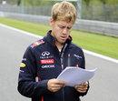 Sebastian Vettel studies some notes as he walks the track