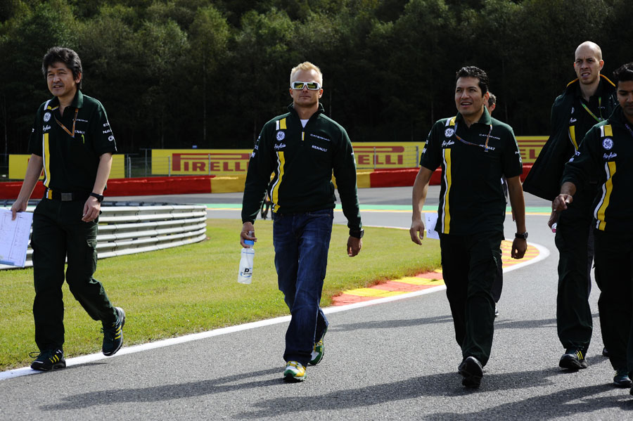 Heikki Kovalainen walks the track with his Caterham team