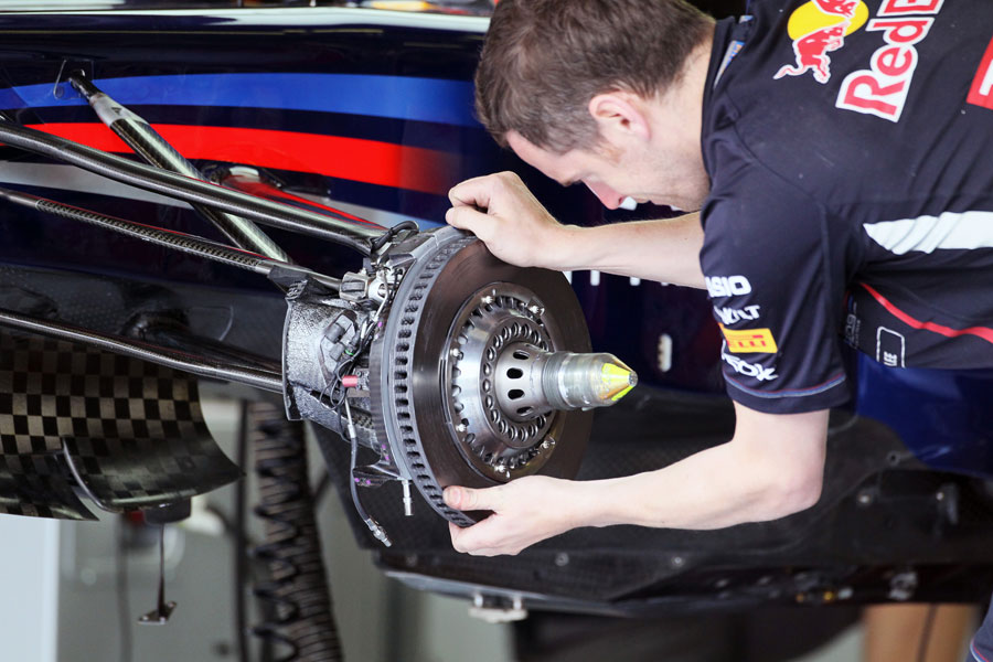 A Red Bull mechanics fits a brake disc