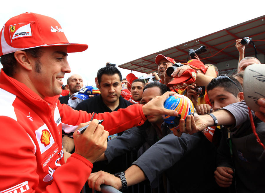 Fernando Alonso signs autographs for the fans in the pit lane