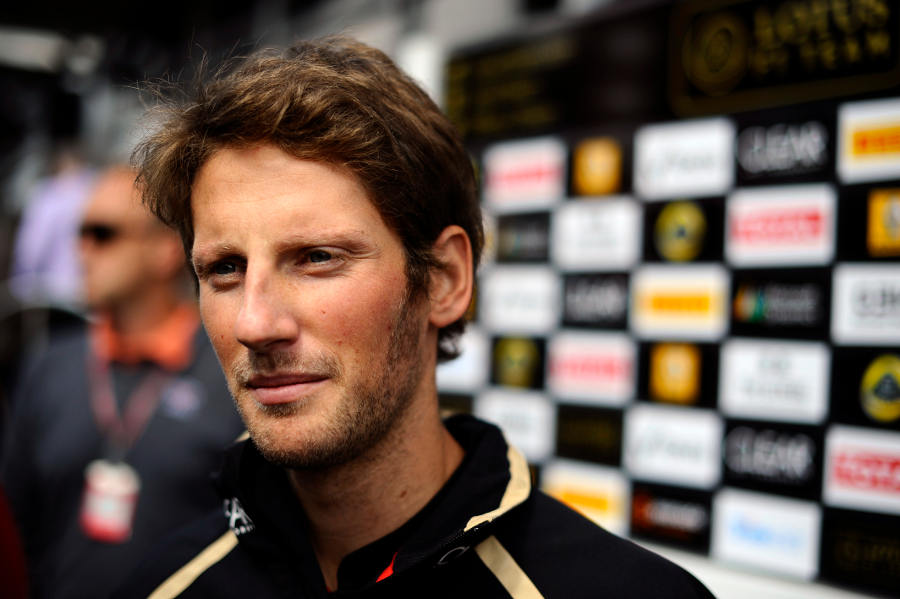 Romain Grosjean speaks to the press outside the Lotus motorhome