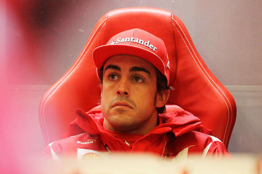 Fernando Alonso watches on from the sanctuary of the Ferrari garage