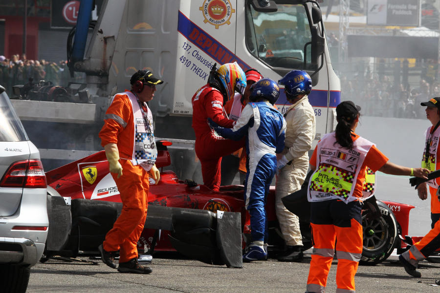 Championship leader Fernando Alonso is helped out of his car after a first corner crash