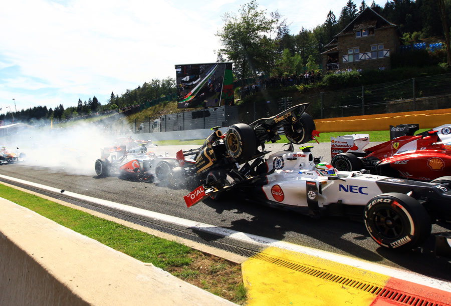 Romain Grosjean mounts the back of Sergio Perez's Sauber at the first corner