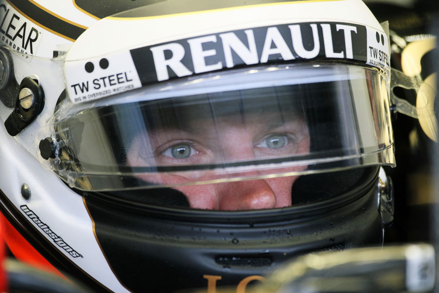 Kimi Raikkonen stares while waiting in the Lotus garage