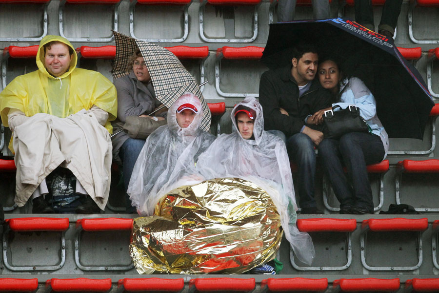 Fans shelter against the weather during Friday practice