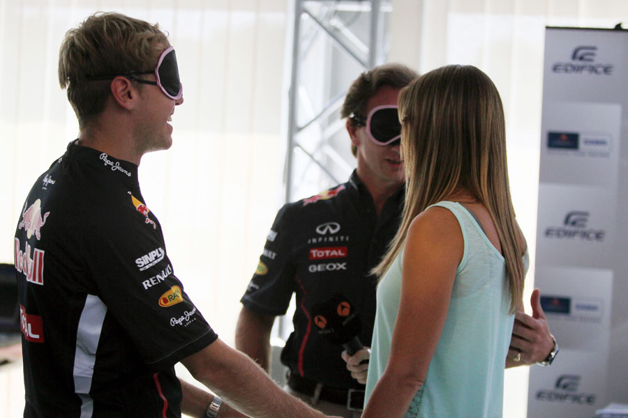 Sebastian Vettel and Christian Horner take part in a blindfold round during a sponsors' quiz in the paddock on Thursday