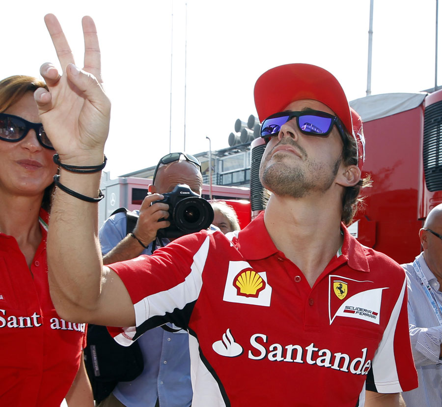 Fernando Alonso salutes fans in the paddock