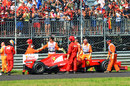 Fernando Alonso looks over his Ferrari after an engine problem