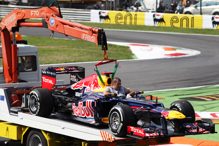 Sebastian Vettel's Red Bull is returned to the pit lane